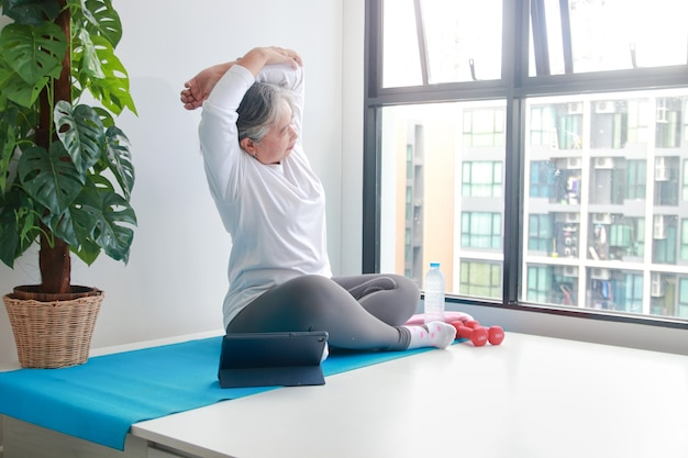 Les femmes âgées asiatiques font de l'exercice à la maison faites des étirements des bras selon l'entraîneur sur la tablette. par vidéo en ligne. concept de soins de santé pour les personnes âgées