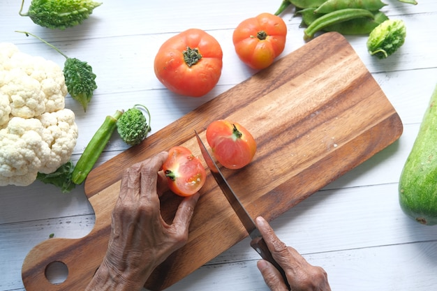 Les femmes âgées couper les tomates sur une planche à découper de haut en bas