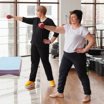 Les femmes âgées exercent avec des poids