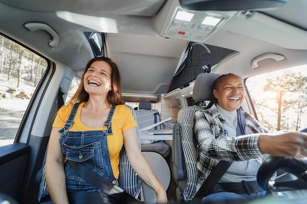 Femmes âgées multiraciales s'amusant sur la route dans un camping-car - focus sur le visage de la femme gauche
