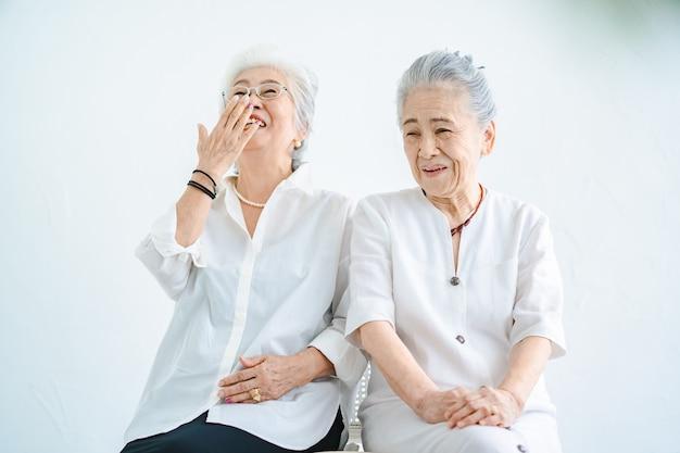 Femmes âgées parlant avec un sourire dans la salle lumineuse