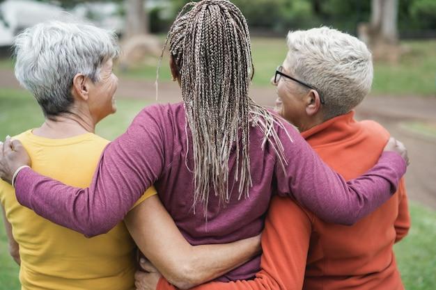 Les femmes âgées s'amusant avant la classe de yoga au parc extérieur - focus sur la tête de dame centrale
