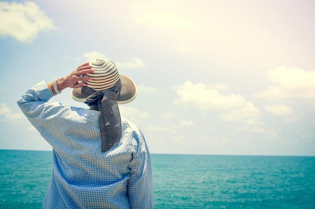 Les femmes âgées se rendent à la mer pour se détendre. debout, faisant demi-tour, tenant le chapeau en regardant la mer