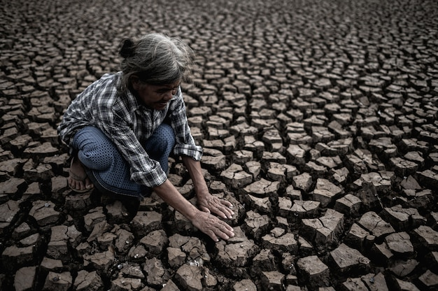 Les femmes âgées sont assises en regardant leurs mains, touchant le sol par temps sec, le réchauffement climatique