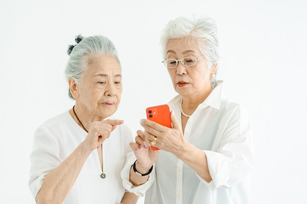 Femmes âgées utilisant un smartphone par essais et erreurs
