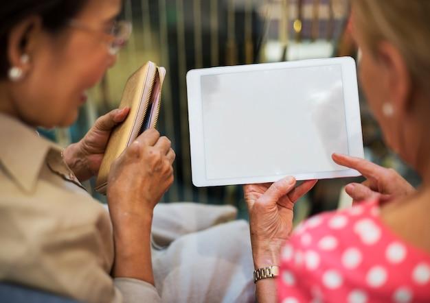 Les femmes âgées utilisent les mains tenir la tablette