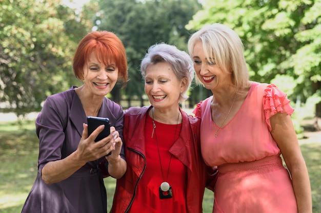Femmes âgées vérifiant un téléphone ensemble