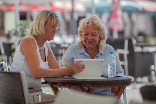 Femmes aînées, délassant, dans, café, et, utilisation, tablette numérique
