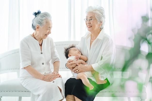 Femmes aînées étreignant le bébé nouveau-né dans la chambre