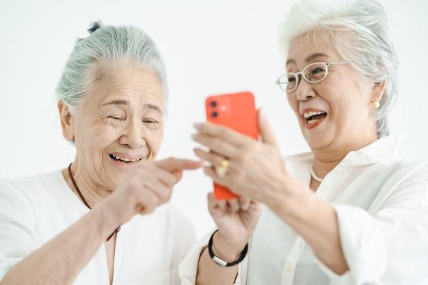 Femmes aînées regardant des écrans de smartphone avec un sourire