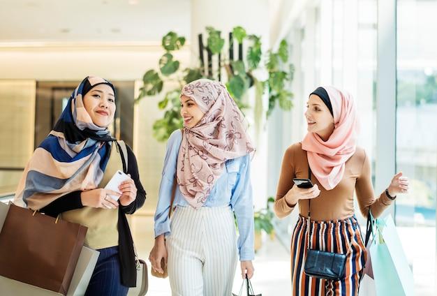 Femmes amies islamiques marchant et discutant ensemble