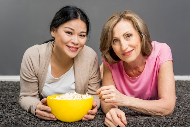 Femmes à angle élevé sur le plancher avec bol de pop-corn