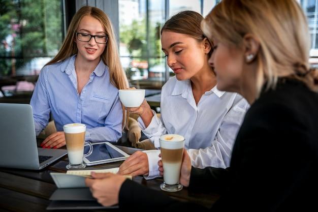Femmes à angle élevé travaillant et buvant du café