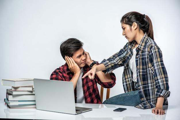 Les femmes apprennent aux hommes à travailler avec des ordinateurs portables au travail.
