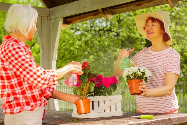 Femmes arrosant des fleurs. des femmes élégantes et attrayantes vivant dans un quartier arrosant des fleurs ensemble