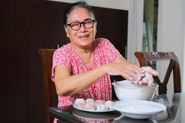 Femmes asiatiques âgées souriantes heureuses tout en préparant des aliments à cuire
