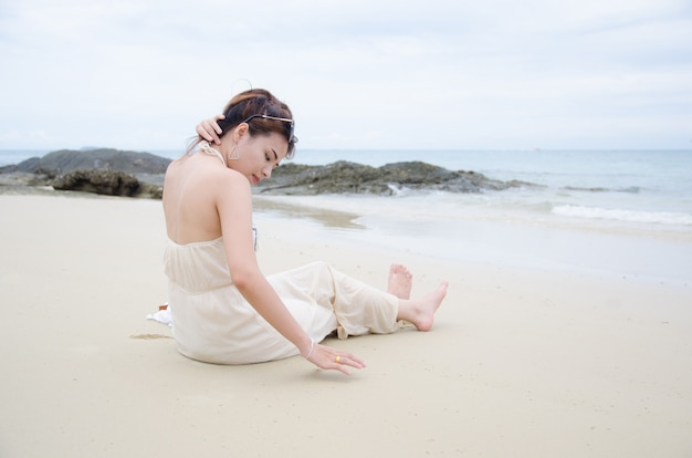 Femmes asiatiques assis sur la plage de la mer et touche ses cheveux