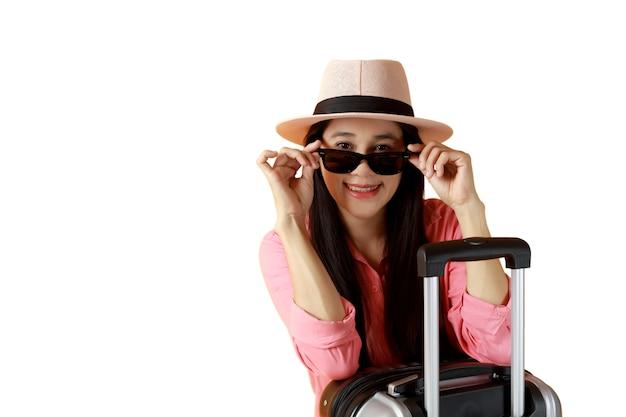 Les femmes asiatiques aux cheveux longs portent un chapeau, des lunettes de soleil, un sac de voyage et une main tenant des lunettes.