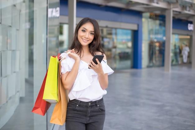 Les femmes asiatiques et belle fille tient des sacs au supermarché / centre commercial