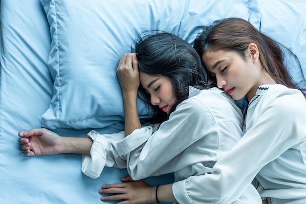 Femmes asiatiques dormant sur le lit ensemble. lesbian lovers et couple concept. thème de personnes