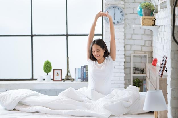 Femmes asiatiques elle est au lit et se réveillait le matin. elle se sentait très rafraîchie.