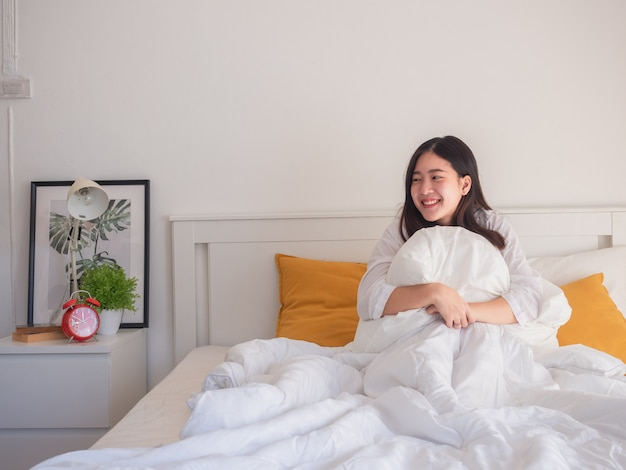 Les femmes asiatiques embrassent des oreillers sur le lit le matin