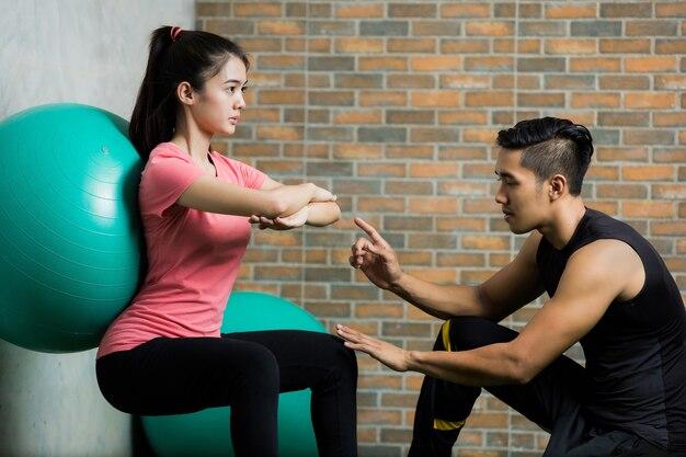 Les femmes asiatiques enseignent l'exercice d'entraîneur avec la boule de pilates