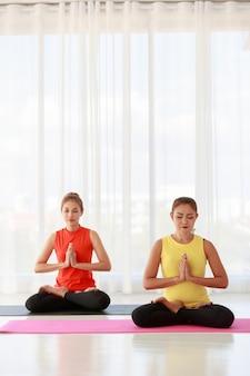 Les femmes asiatiques ferment les yeux et serrent les mains tout en méditant dans la pose de lotus pendant une séance de yoga en studio