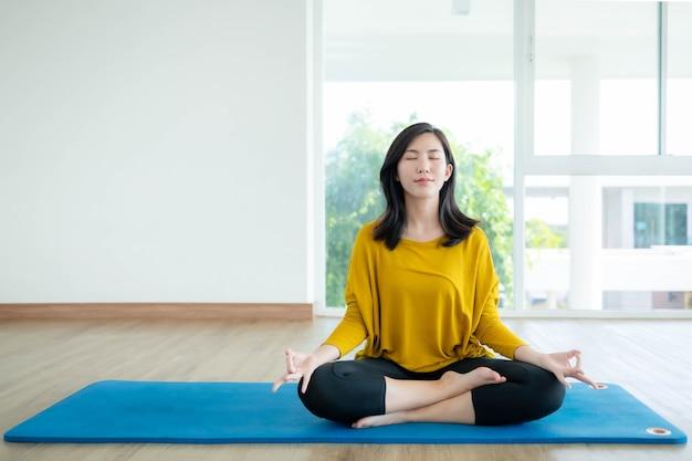 Les femmes asiatiques font du yoga à la maison pour se faire un bon corps.