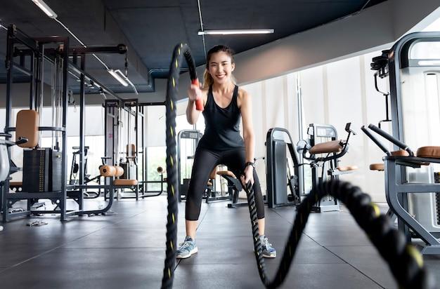 Les femmes asiatiques font de l'exercice dans la salle de sport pour passer au crible l'eau du cuir, gardant leur corps en bonne santé.