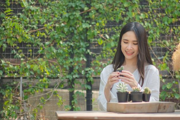 Les femmes asiatiques de jardinage à domicile cactus dans le jardin d'accueil