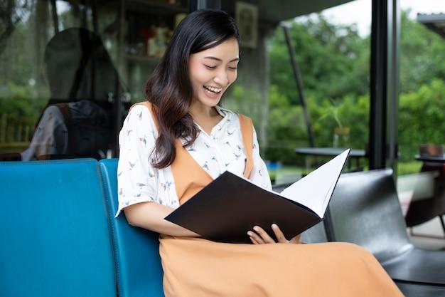 Femmes asiatiques lisant et souriant et heureux détente dans un café