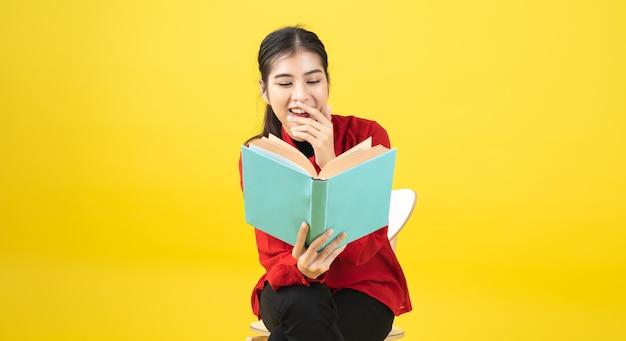 Les femmes asiatiques lisent un livre ou un roman, apprécient et heureuses, la femme ouvre un livre dans la main et le lit accidentellement sur fond jaune avec espace de copie.