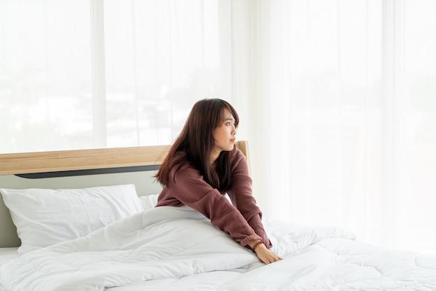 Les femmes asiatiques sur le lit et se réveiller le matin