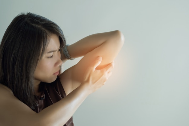 Femmes asiatiques mal au coude, fille douleur au coude sur fond blanc