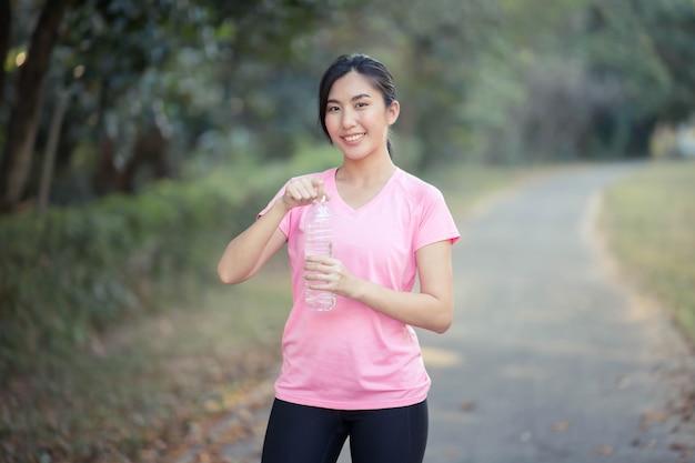 Les femmes asiatiques ouvrent l'eau potable