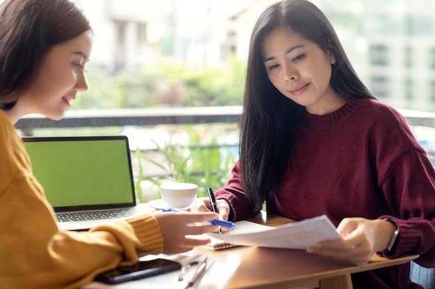Femmes asiatiques parler avec travailler avec un nouveau projet au café. concept de réunion de travail d'équipe.