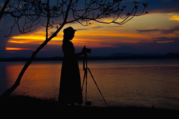 Femmes asiatiques photographiant se sentent bien sur la vue sur le lac et les montagnes avec un chapeau au moment des vacances