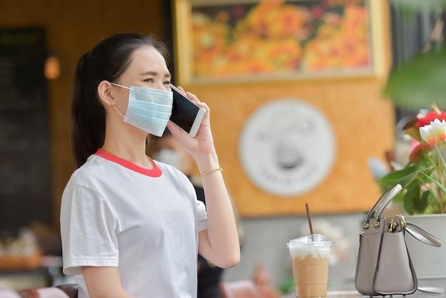 Les femmes asiatiques portent un masque chirurgical et utilisent un smartphone au café