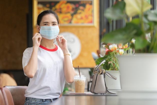 Les femmes asiatiques portent un masque facial assis dans un café-café