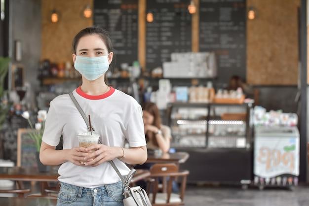 Les femmes asiatiques portent un masque facial dans un café-café