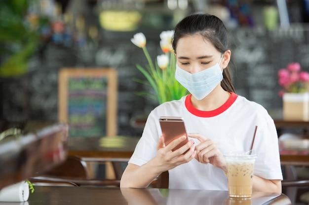 Les femmes asiatiques portent un masque médical et utilisent un téléphone portable assis dans un café