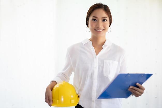 Des femmes asiatiques qui inspectent et travaillent et détiennent des plans au bureau
