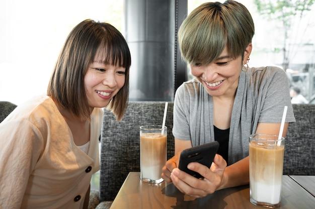 Femmes asiatiques regardant quelque chose au téléphone