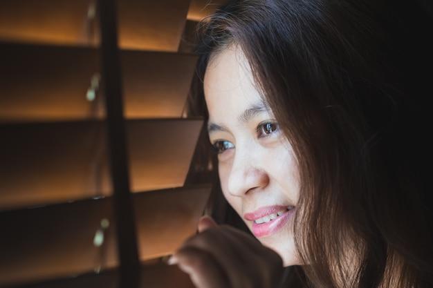 Femmes asiatiques regardent par la fenêtre