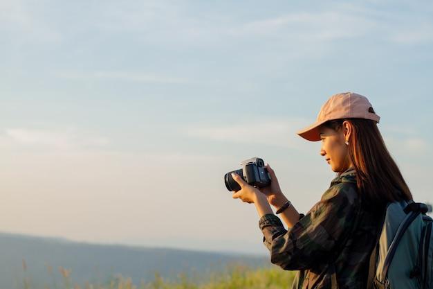 Femmes asiatiques avec sac à dos en prenant une photo sur la vue au sommet de la montagne au bord de la mer au lever du soleil