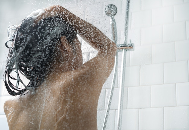 Femmes asiatiques se baignant et elle se lavait et se lavait les cheveux