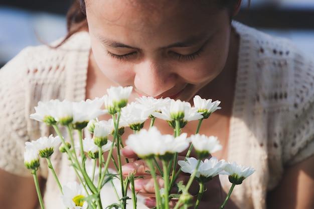 Les femmes asiatiques sentent les fleurs de chrysanthème blanc dans le jardin