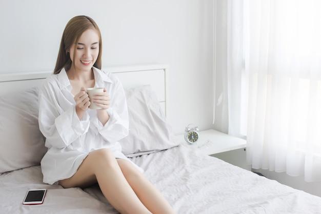 Femmes asiatiques sexy en chemise blanche buvant du café et se réveiller dans son lit