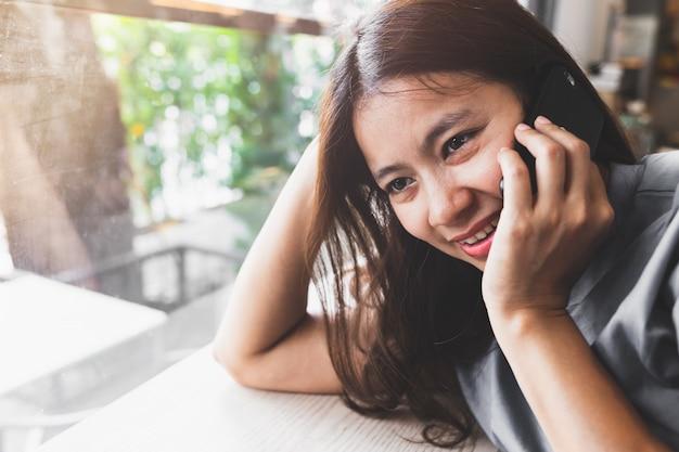 Les femmes asiatiques sont heureuses de parler aux téléphones mobiles dans les cafés